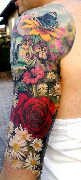 Un #tatuaje colorido de flores para hombre! Aquí en esta foto de tatuajes vemos el tattoo de varias flores, margaritas, violetas, rosas y más variedades de flores a color, un pájaro picaflor y una mariposa azul, negra y blanca en un tatuaje que es toda una obra de arte tatuada en la piel de este hombre. #Tattoo