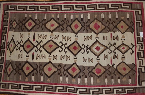 """Native American Rug 101.Description: Navajo Weaving. 6'10"""" x 4'2"""". Elaborate Teec Nos Pos design with dozens of feathers and a Greek key border. Woven from all home spun wool. Circa 1920. Excellent Co"""