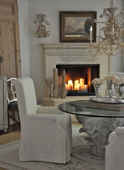French Country interior design style in a beautifully romantic dining room. Slipcovered dining chairs and a glowing fireplace enhance this Santa Monica beach cottage with design by Brooke Giannetti. #frenchcountry #diningroom #romanticdecor #fireplace #brookegiannetti #giannettihome #oldworld #whitedecor