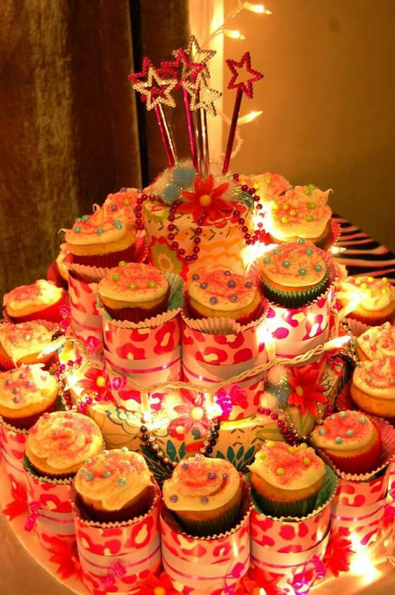 Cupcake Tower and Cupcakes I made for daughter's 10th birthday disco party. Materials; poster board, foam board, wrapping paper, bead necklaces, silk flowers, puff balls, wands