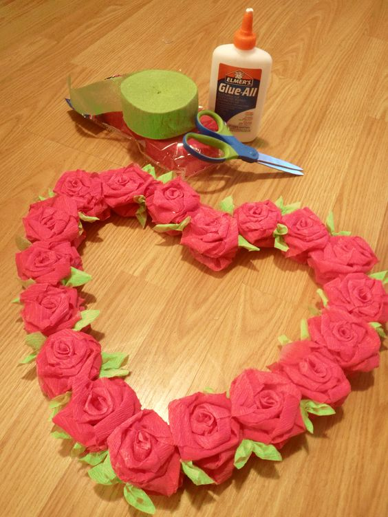 """From Rachel MacNaught:  """"okay a little excited about this craft i'm getting paid to do them for work as well as 4 giant rose topiaries. valentine's wreath for under $2.   all you need is glue, crepe paper and a box to cut the heart shape out.   crepe paper roses are easy to make, just wind paper around your finger, twisting as you go. the leaves i made with little squares folded into a triangle and then glued in the middle to cover the gaps the roses left on the cardboard. cannot be any…"""