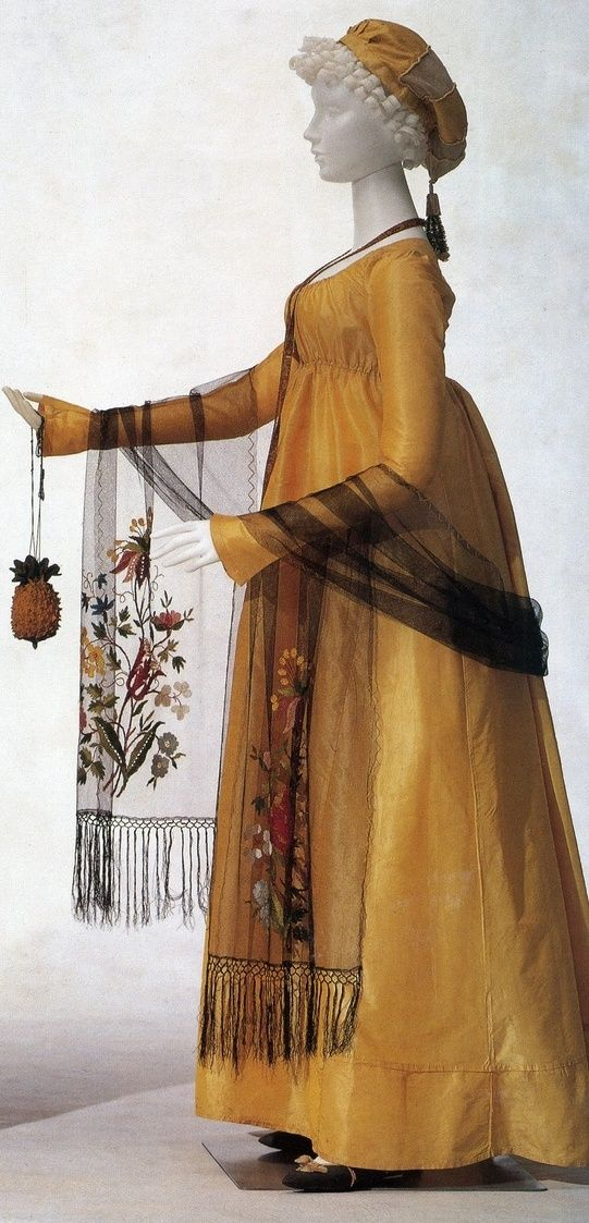 """Gown: ca. 1800, silk taffeta with silk net shawl with an embroidered floral motif and silk fringe as well as hat silk net and pongee. With pineapple reticule.  From the Kyoto Costume Institute, """"Fashion: The Collection of the Kyoto Costume Institute"""":"""