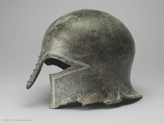 The shape, decoration,  craftsmanship of this bronze helmet suggest that it is the work of a Corinthian craftsman  can be dated circa 650-625 BC. The Corinthian helmet was widespread in Greece from the 7th century BC onward. Its origin is ascribed to the workshops in Argos, but it is frequently portrayed on Corinthian vases,  substantial quantities seem to have been made at Corinth. The helmet was part of the equipment of hoplites... heavily armed soldiers