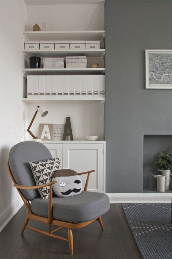 a handsome mid century chair in a grey on grey room. lovely, but it needs some beautiful bright accessories!