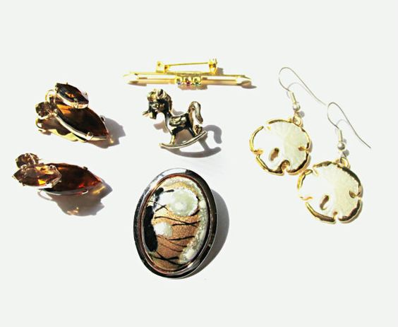 A lot of various vintage costume jewelry pieces. All look to be in good condition with light wear:  -2 1/4 inch, oval, gold glitter, plastic brooch - 1 3/4 inch, silver tone metal, rhinestone, enamel, Shriners, maple leaf brooch - very old, 2 1/2 inch, brass, Native American arrow brooch with glass stone (stone has a small chip) - 8 inch long, silver tone metal, coin link, ceramic scarab beetle bracelet - 1 1/8 inch, silver tone metal, handmade enamel, oval, modernist pin - 7 inch, newer…