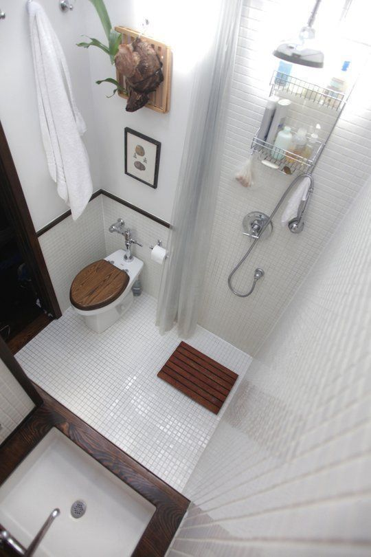 All-In-One Awesome The shower is incorporated right into the greater overall space in this diminutive bathroom. White 1x1 inch tile is used on both the floor and walls throughout to bring it all together, while a dark wood counter, bath mat and toilet seat bring warmth to the room.
