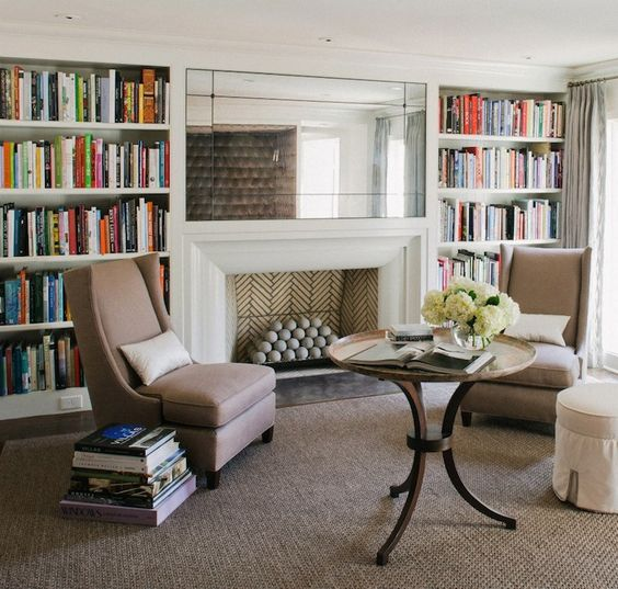 chic home library with floor to ceiling built in bookcases flanking french mirror over fireplace built home library
