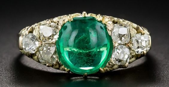 Like a sweet and luscious lime flavored candy, a bright crystalline green, round cabochon emerald, weighing 2.00 carats, glows between sparkling white trios of old mine-cut diamonds, in this superb and stunning antique jewel, dating from the-turn-of-the-last century. Elegantly handcrafted in rosy-yellow gold with a yellow gold center setting with a stylized scroll motif gallery.