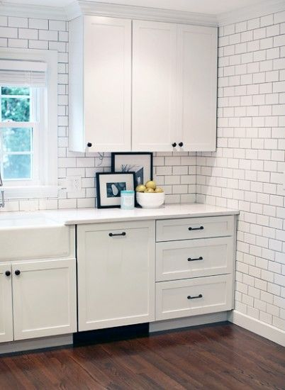 White cabinets with black oil rubbed bronze hardware and a for Black kitchen cabinets white subway tile