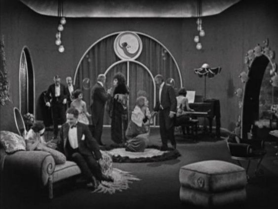 love the detail over the door in the arches, but also the little camellia on the ottoman in the foreground. this is a scene from Camille, 1921