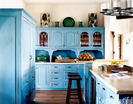 """I wanted this jolt of color to emphasize that the kitchen is the joyful heart of the house,"" says designer Christina Rottman. To achieve it, a blackened umber glaze was applied to the cabinets, then painted over with a turquoise glaze. Buffing, stippling, and scraping gave the cabinets a timeworn look. Countertops are limestone. Mikkel Vang  - HouseBeautiful.com"