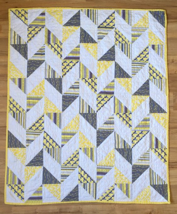 Herringbone Half Square Triangle Baby Quilt | Yellow, gray, and white baby quilt. Half square triangles patchwork pieces are arranged to make a herringbone pattern.: