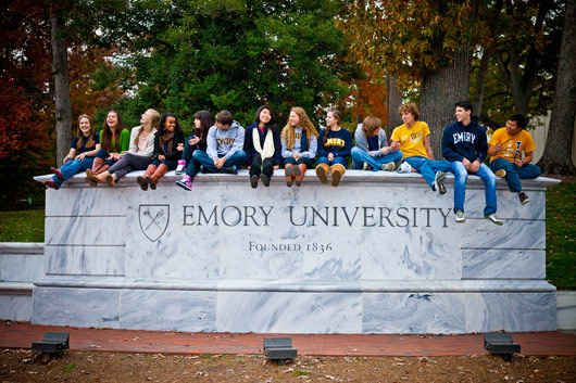 student sitting at the Emory University statue