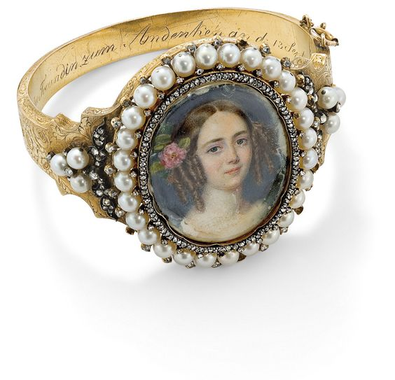 A 19th-century pearl and diamond double-sided portrait bangle  The elaborately foliate engraved hinged bangle composed of a central oval locket containing a portrait plaque of a young girl set within a rose-cut diamond and pearl frame to similarly set rose-cut diamond foliate and pearl shoulder detail, the reverse plaque depicting a similar portrait of a young girl, the inside engraved and dated 1803–38, inner diameter 6 cm, with safety chain.: