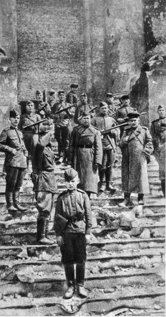 Troops of the 150th Infantry Division of the Red Army strike a pose on the steps of the ruined Reichstag in Berlin. In the foreground, the 14-year boy in uniform is the adopted son of the division's Artemenkov Regiment, May 1945.:
