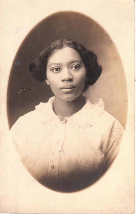 Vintage photo postcard featuring a portrait of a pretty young African American…