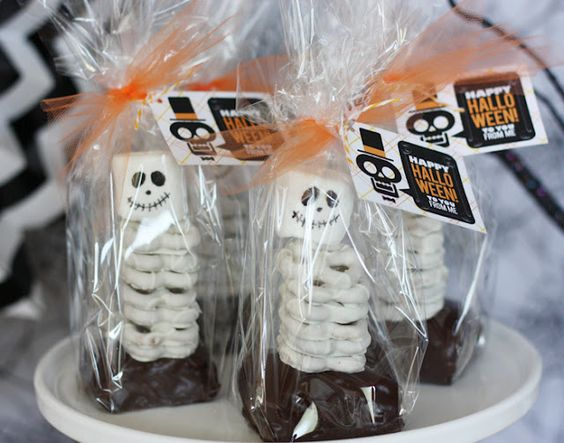 Our Brownie and pretzel skeletons were a spooktacular edition. We made a pan of brownies in a square pan because we wanted them thick, cutting them into squares (don't forget to cut the edges off). Then covered them in ganache. Place a short bamboo skewer or sucker stick close to the back and pile white chocolate pretzels. Top with a marshmallow with a cute skeleton face (drawn on by editable markers) and package with our fun skeleton tag.