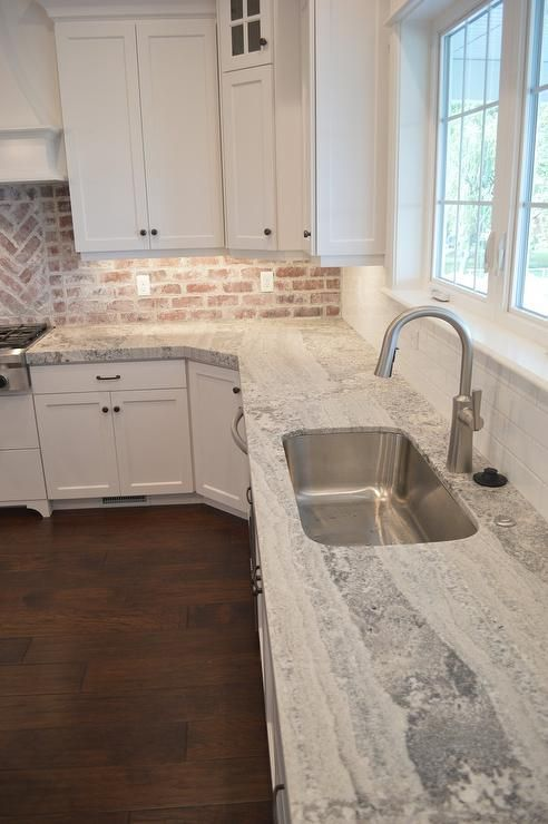 The larger patches to these quartzite countertops make it stand out against the white of the rest of this kitchen. It even pairs very well with the old style brick in the backsplash.