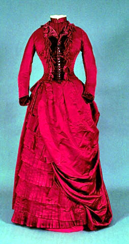 Dress, Canadian, 1878. Red shot silk bodice w/burgundy shell buttons at center; real opening at right w/16 hooks & eyelets. Small revers collar. Neckband edged w/2 white net ruffles. Burgundy velvet bows on bodice & cuffs. Fitted sleeve w/gathering at elbow & cuff w/curved ends. Small peplum at center back. Lined w/cotton twill; boned. Foundation & asymmetrical overskirt of red shot silk. Knife pleat frill of silk at skirt bottom. Univ. of Alberta