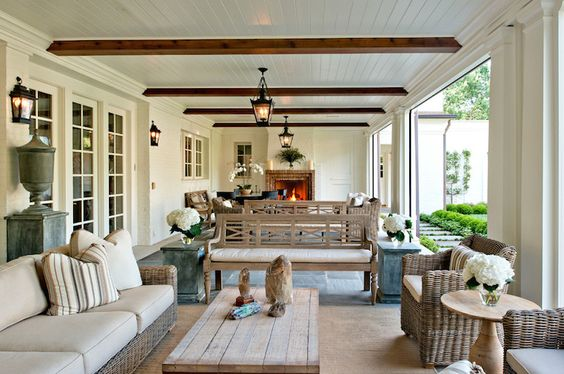 Long covered patio features beadboard ceiling dotted with stained wood beams over two separate and distinct sitting areas.