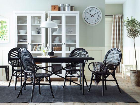 Comedor con una mesa negra y sillas de ratán. dos vitrinas blancas ...