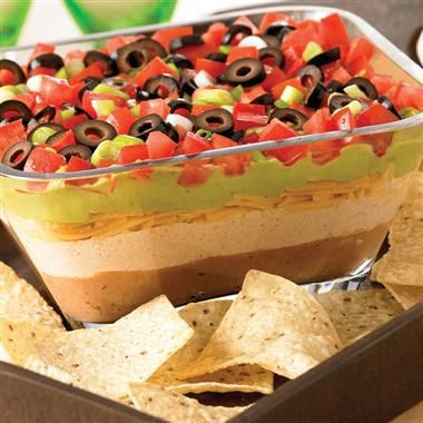 Seven Layer Fiesta Dip ~ Top with layers of cheese, guacamole, tomatoes, onions and olives... Serve with tortilla chips