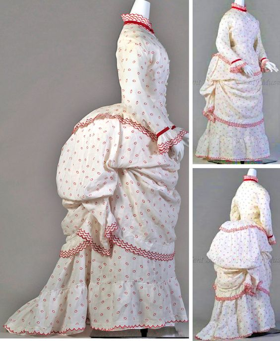 Day dress, American (attrib.), ca. 1873-77. White cotton printed with red circles. Bodice: fitted over hips, ruffled edge, long sleeves. Skirt: bustle with white cotton and red trim. Overskirt: as draped apron. Kent State Univ. Museum