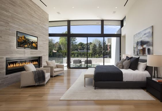 This sensational modern bedroom features simple clean lines with complementary charcoals and blacks that contrast brilliantly with the lighter whites and creams. A stunning gray brick wall houses a long, rectangular fireplace, while a flat screen TV is wall mounted and positioned for easy viewing. Large picture windows allow a glimpse into the clean and minimalist outdoor patio.