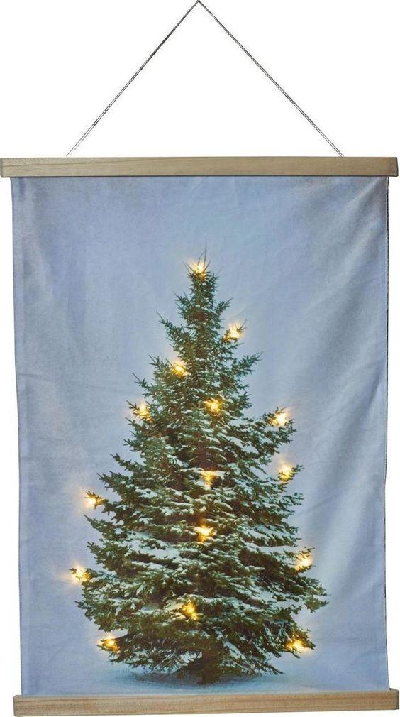 Heeft u geen zin om de kerstboom op te zetten dit jaar?Dan is dit de ideale oplossing om toch een kerstsfeer te creëren. Deze kerstboom op doek met de afmeting 52 x 70 cm is voorzien van 15 LED-lampjes die werken op 2x AA batterijen.