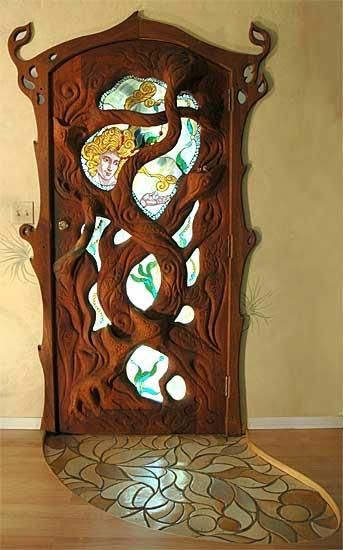 carved wood door that looks like a tree with stained glass inserts