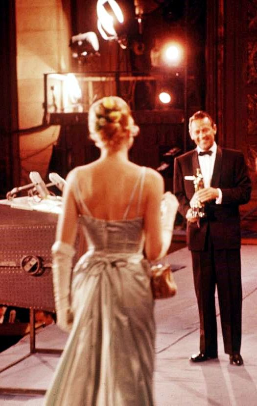 William Holden awaits Grace Kelly with her Oscar for The Country Girl, in which he was her co-star, 30 March 1955