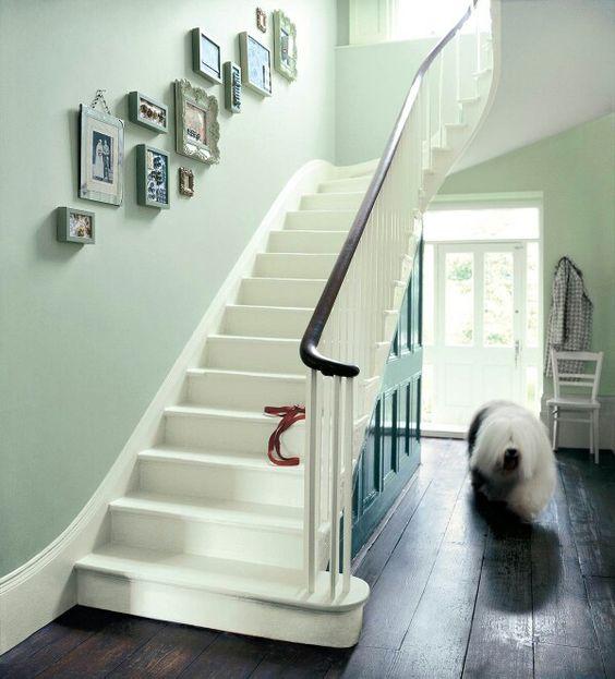 Lichtgroen op de wanden en donkergroene lak onder de trap. Let ook op de lijsten op de wand, deze lopen mee met de vorm van de trap, heel decoratief.