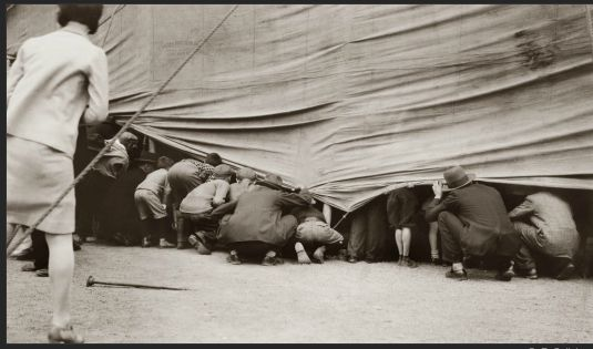 1929 men peaking under a circus tent.  Story writes itself