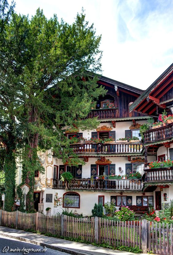 Wer kennt es nicht, das stattliche zweigiebelige Haus in der Rosenstraße Tegernsee. Ausgebaut im Heimatstil mit reich geschnitzten Lauben, Giebellauben, Lüftlmalereien und Standerker.