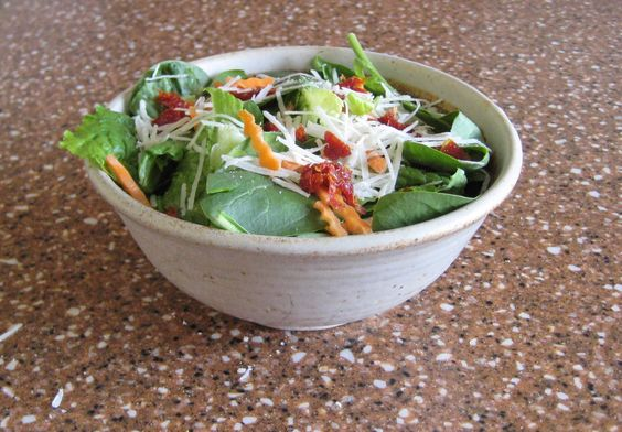Salad done right.  Romaine lettuce, spinach, diced sun-dried tomatoes, a few carrots, a shredded hard cheese and some home-made vinaigrette dressing.  Simple and refreshing.