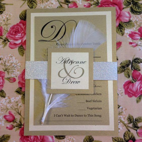 Silver and gold wedding invitation suite with feather detail.