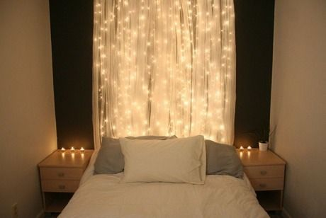 In place of a headboard or to light up any wall! - Strings of Christmas lights behind a sheer curtain.