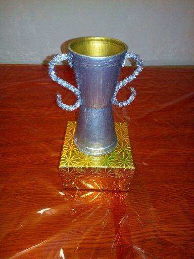 Copa trofeo. Materiales: vasos de corcho blanco, limpiapipas, caja cuadrada, tempera plateada y tempera dorada.