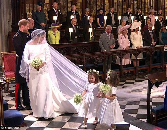 When Meghan appeared through the doors of the chapel, sunlight streaming in behind her, she turned to smile and wave at the children who were standing to her right behind the door