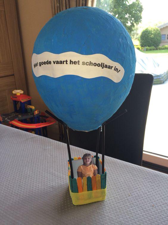 Luchtballon. Ballon van papier-maché geschilderd. De mand is het onderste van een melkbrick bekleed met gekleurde stokjes en crepapier. 4 rietjes waar de ballon op rust. Veel knutselplezier