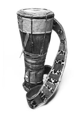 Batà Nigeria  Description : Technical description: Wooden concial shell; heads tensioned by leather thongs bound round at waist to further tension the thongs running from head to head. There is some unceratainty as to whether the smaller head is playedHead diameters 190, 110. Measurements : 555