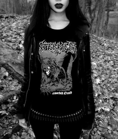Metalhead girl in band shirt,bullet belt and leather jacket.