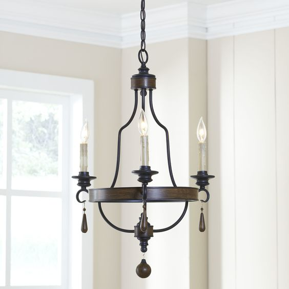 Maynard Chandelier | Bands of rustic finishing complements the dark metal on this shapely overhead chandelier. Teardrop accents and a hanging ball finial enhance the elegant style and give it a more grand feel for your room.