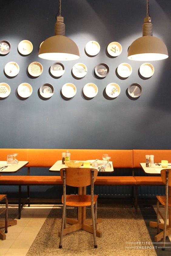 Banco corrido naranja sobre pared gris azulado decorada con platos. depasta kantine rotterdam