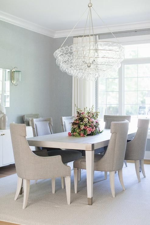A Glass Tiered Chandelier Illuminates A White And Gray Dining Table Placed On A Gra Glass Dining Table Decor White Glass Dining Table Fabric Dining Room Chairs