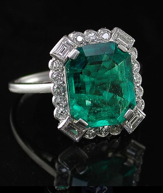 Art Deco Emerald An Art Deco era emerald and diamond ring. The octagonal emerald measuring 11.4 x 9.58mm, weight approximately 3.00 ct. Set within a decorative halo border of four baguette cut and sixteen old brilliant cut diamonds. Platinum. An Art Deco original, circa 1925.