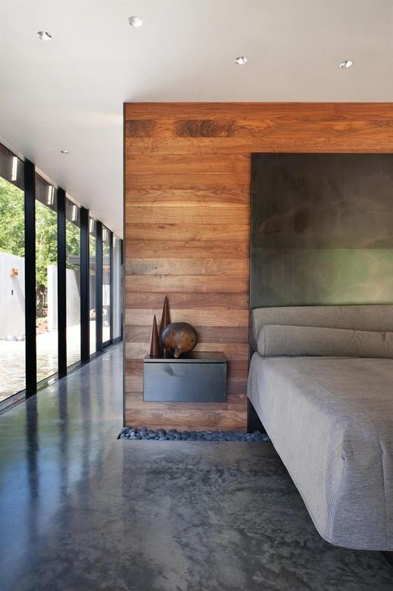 A band of rocks intersects the ground and wall plane in the master bedroom. Local walnut visually warms the concrete floors.