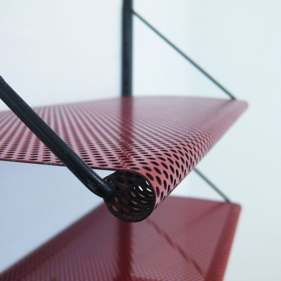 Red perforated wall shelving unit