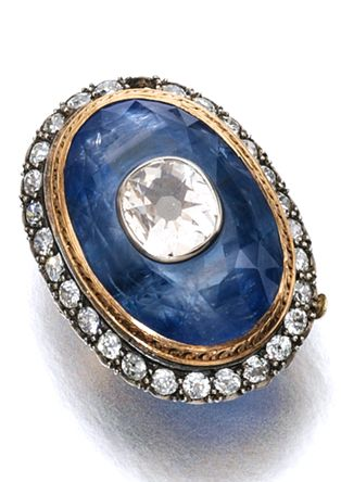 SAPPHIRE AND DIAMOND RING, CIRCA 1900 The oval sapphire inset with a cushion-shaped diamond, within a surround of circular-cut diamonds, size 43, one diamond deficient, central jewel detachable.