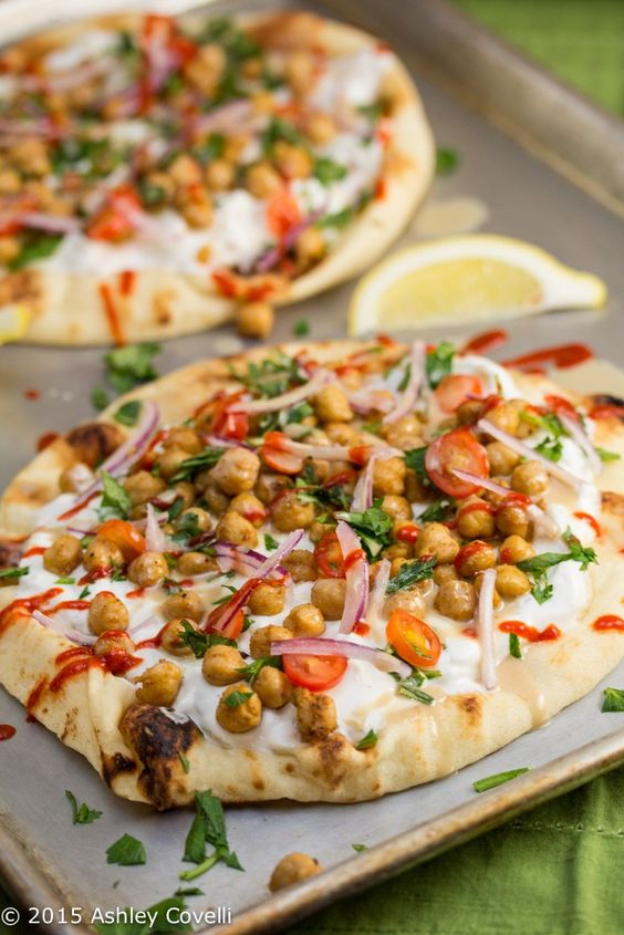 Naan is covered in garlicky tzatziki sauce and covered with Middle Eastern-spiced chickpeas, tahini, fresh herbs and Sriracha in this street food/comfort food mashup.